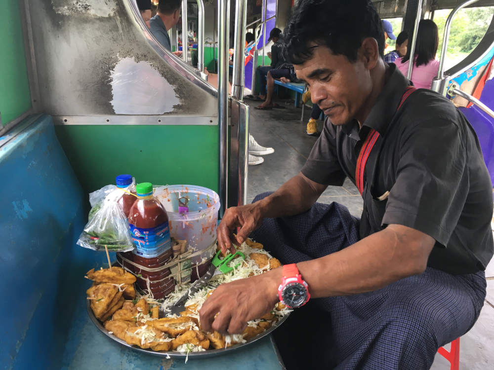 Ein fliegender Händler beim Zubereiten seiner Spezialitäten im Zug.