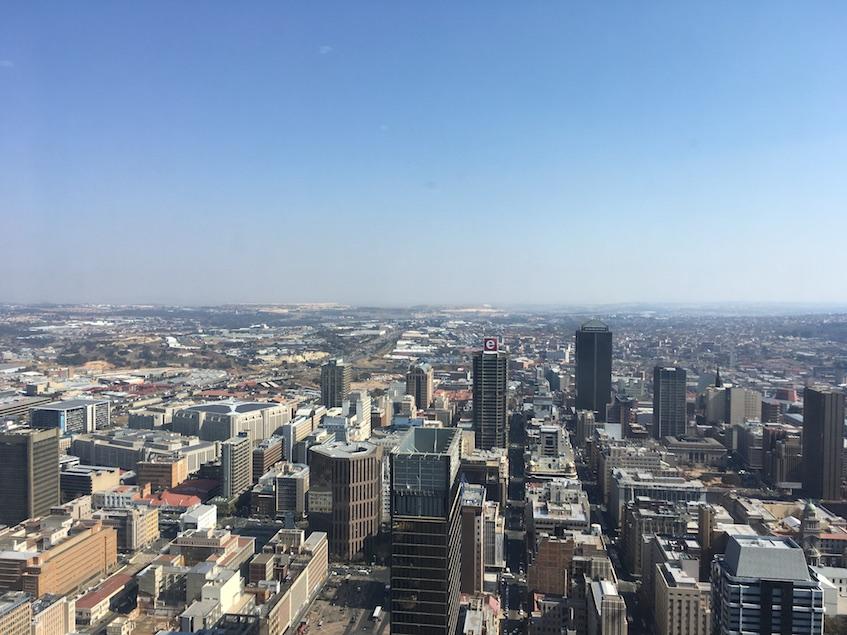 Johannesburg von oben, im Hintergrund die für Johannesburg typischen gelben Hügel, die noch von der Goldgräberzeit zeugen. Es handelt sich um Abraumhalden der Goldminen. Mit neuer Technologie wird darin heute nach Goldresten gesucht.