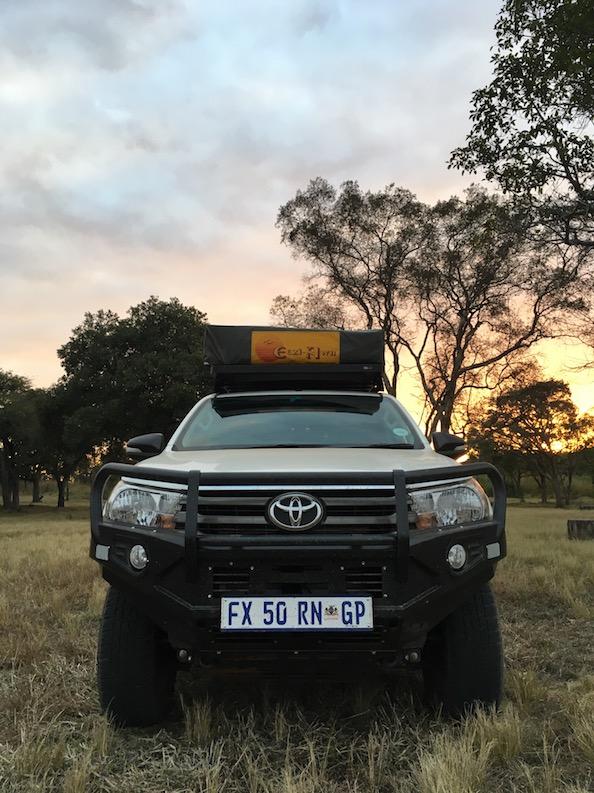 Great Zimbabwe – im Sonnenuntergang sieht selbst ein Auto nach was aus. Noch... Später, während all der Safaris wird es auch innen so dreckig sein, dass wir mit frisch gewaschenen Händen einsteigen können, und drei Minuten später schwarze Ränder unter den Nägeln haben.